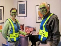 Two public health volunteers with green face paint to look like zombies
